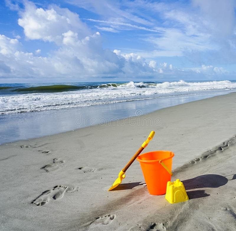 A Shovel and Pail on the Beach. Ready to build a sandcastle with this shovel and pail on the beach stock image