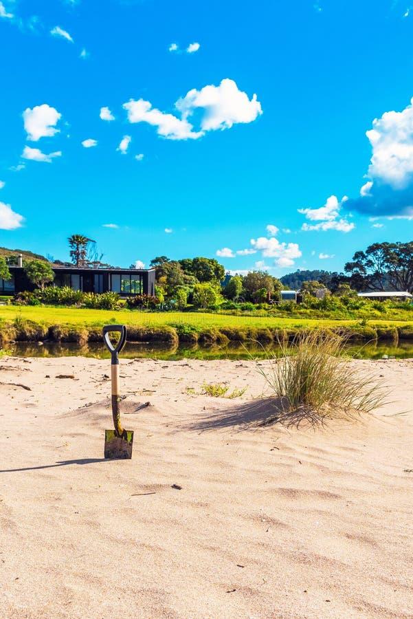 Shovel on a sandy beach, Coromandel, New Zealand. Vertical.  stock image