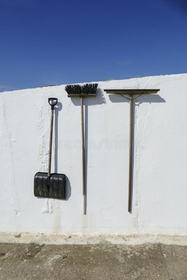 Shovel, snowy shovel, broom and water renderer hang on a  wall royalty free stock photos