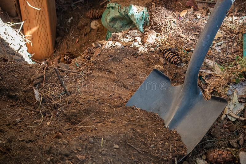 Shovel sticking out of pile of dirt on construction site royalty free stock image