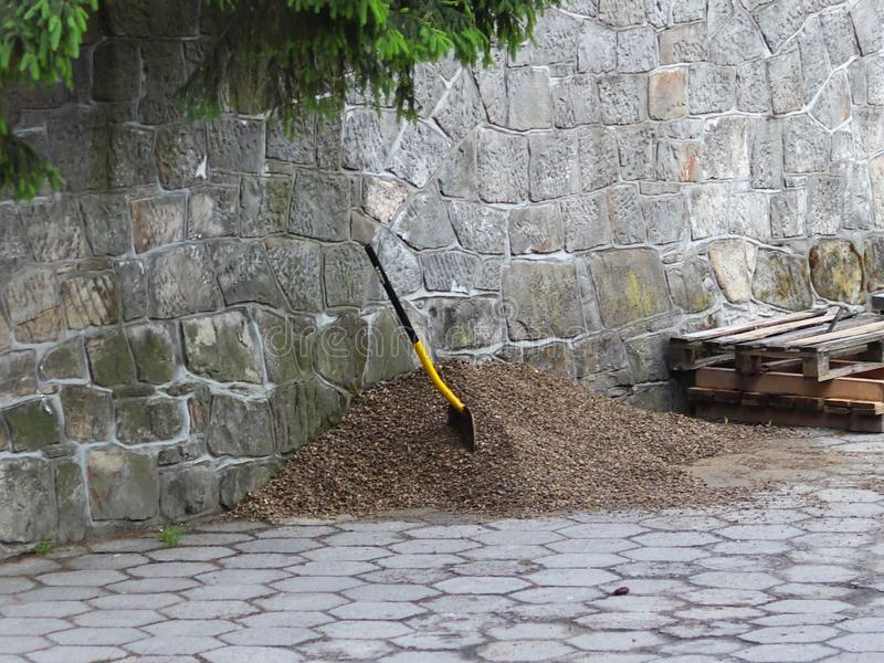A shovel stuck in a pile of rubble near the stone gray walls. Construction and repair work. Construction Materials. stock photos