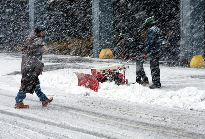 Shoveling snow in blizzard stock images