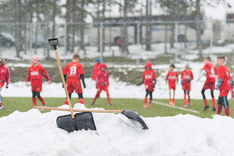 Shovels in the pile of snow after cleaning snow from the soccer. Field - young kids soccer match during snow fall stock photography