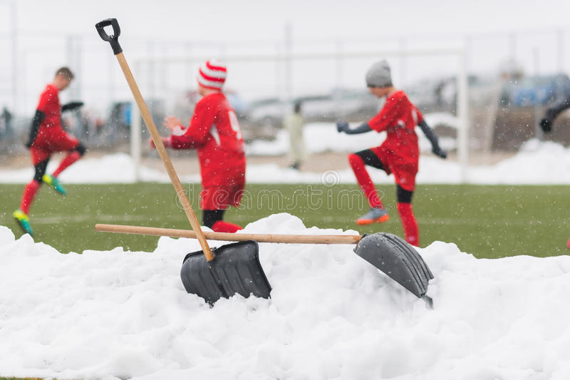 Shovels in the pile of snow after cleaning snow from the soccer. Field - young kids soccer match during snow fall stock photo