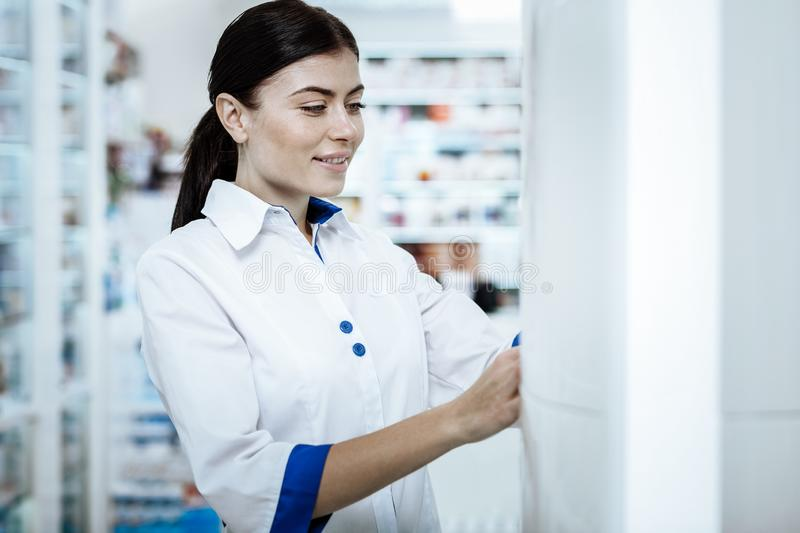 Lovely beaming young woman in a white coat examining the drugstore show case stock photography