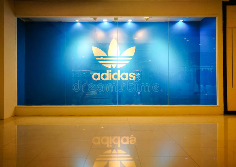 Show för skärm för Adidas originalsymbol på skyltfönstret av detaljisten arkivbilder