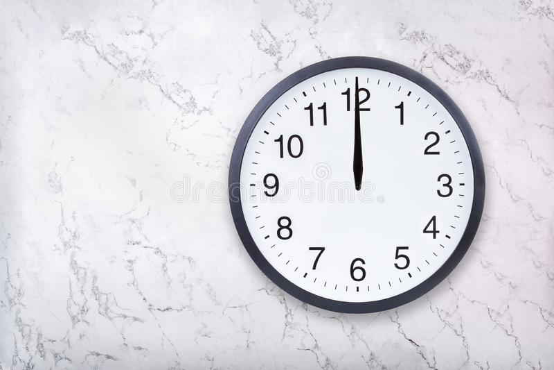 Show för väggklocka det tolv klockanet på vitmarmortextur Middagar eller midnatt för kontorsklockashow royaltyfria bilder