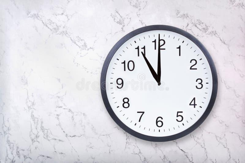 Show för väggklocka elva klockan på vitmarmortextur Kontorsklockashow 11pm eller 11am royaltyfri bild