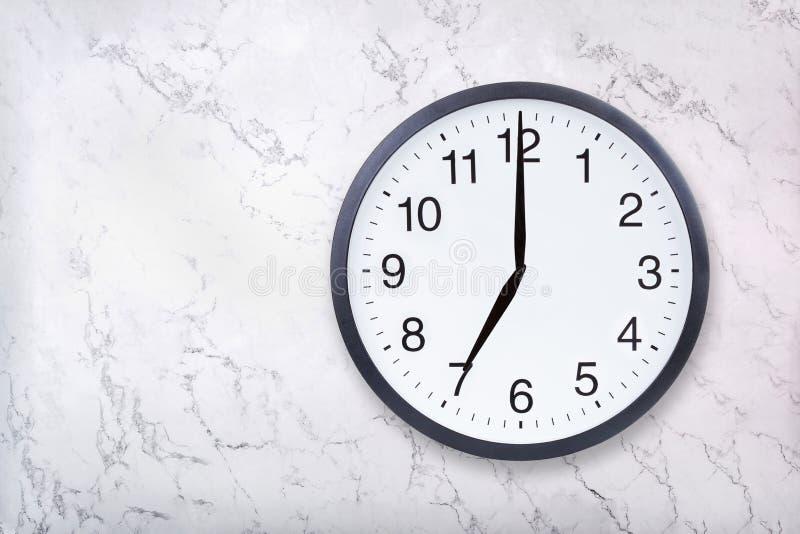 Show för väggklocka sju klockan på vitmarmortextur Kontorsklockashow 7pm eller 7am royaltyfria foton