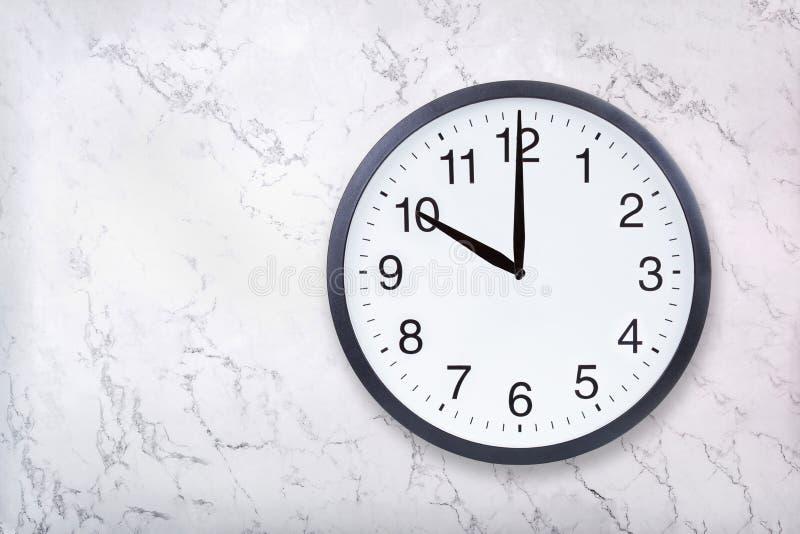 Show för väggklocka tio klockan på vitmarmortextur Kontorsklockashow 10pm eller 10am arkivbilder