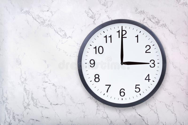 Show för väggklocka tre klockan på vitmarmortextur Kontorsklockashow 3pm eller 3am arkivbild