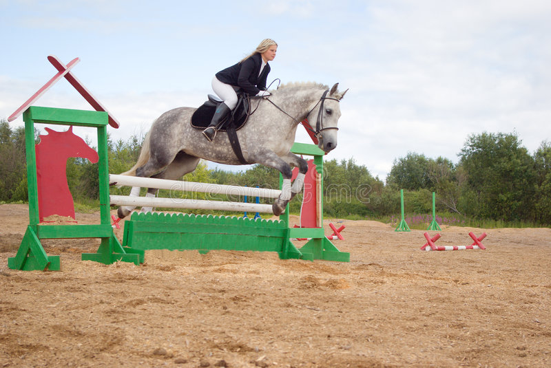 Show jumping. Girl riding horse and jumping stock image