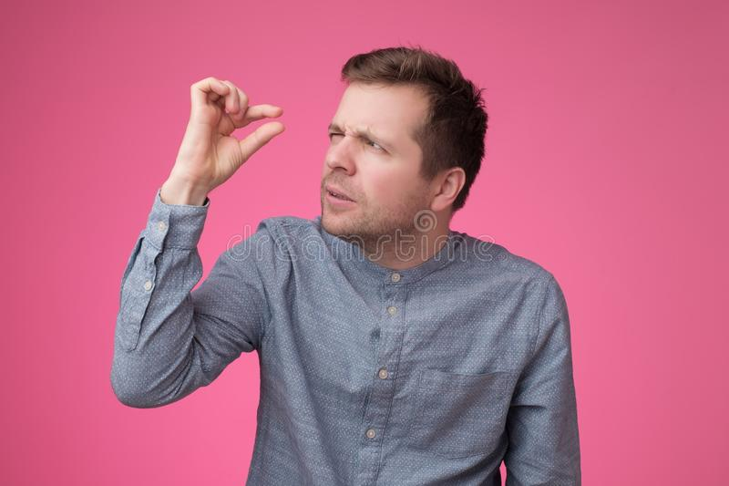An show small size by fingers demonstrate tiny measure, tell about little decreased prices. Caucasian man show small size by fingers demonstrate tiny measure stock photography