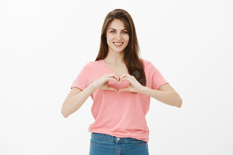 Show some love to closest one. Portrait of happy cute and gently young female in pink t-shirt and jeans, showing heart. Gesture over chest and smiling broadly stock image