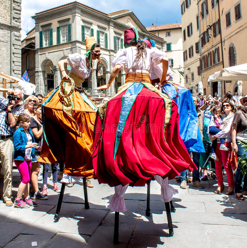 Show of stilt walkers in the street. CORTONA - iTALY - JUNE 01, 2014: show of stilt walkers in the street surrounded by the spectators royalty free stock image