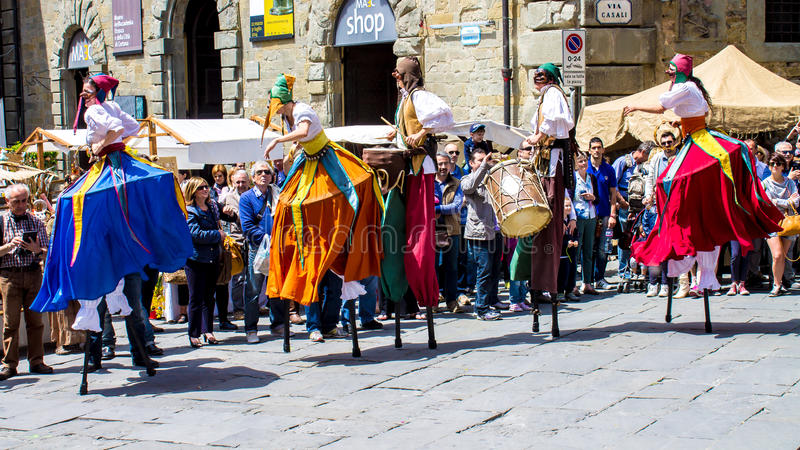 Show of stilt walkers in the street surrounded by the spectators. CORTONA - iTALY - JUNE 01, 2014: show of stilt walkers in the street surrounded by the stock image