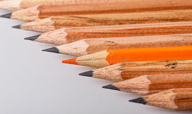 Show up. Color pencil stands out against a series of graphite pencils royalty free stock images
