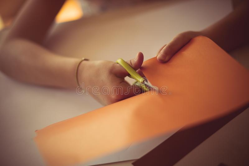 Show your creativity with a paper. Little girl cutting paper. Close up royalty free stock photo