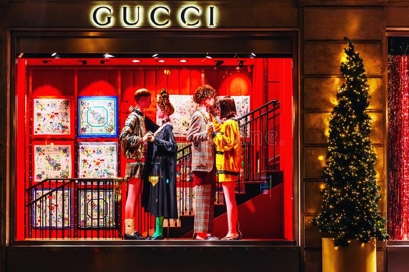 Showcase of Gucci store in Paris in the evening - Luxury shopping concept. PARIS, FRANCE - NOVEMBER 18, 2018: Showcase of Gucci clothes on a mannequins in a stock photos