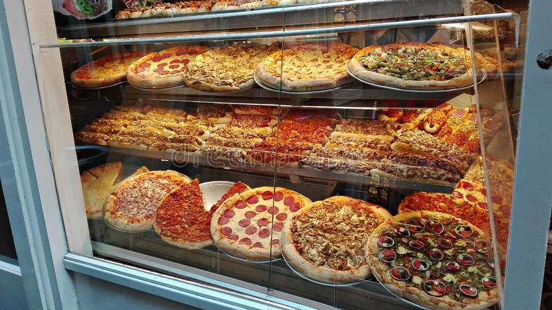 Showcase of a pizzeria full of cooked and stuffed pizzas stock photos