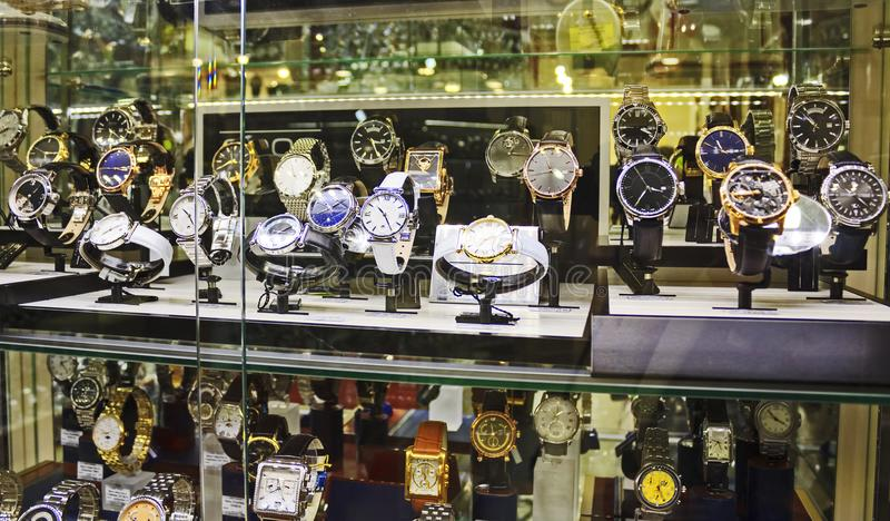 Wrist luxury expensive watches in showcase. Showcase with wrist watches. Collection of expensive luxury watches from gold, silver and leather royalty free stock photo