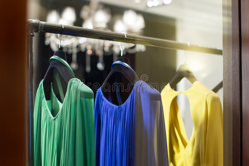 Showcases with dresses. Collection of dresses hanging on hangers stock photos