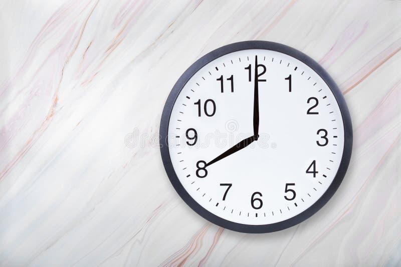 Showen för väggklockan åtta klockan marmorerar på textur Kontorsklockashow 8pm eller 8am royaltyfri fotografi
