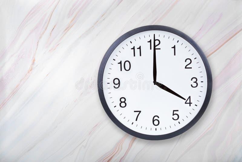 Showen för väggklockan fyra klockan marmorerar på textur Kontorsklockashow 4pm eller 4am arkivbild