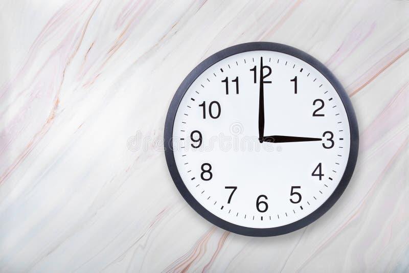 Showen för väggklockan tre klockan marmorerar på textur Kontorsklockashow 3pm eller 3am royaltyfri foto