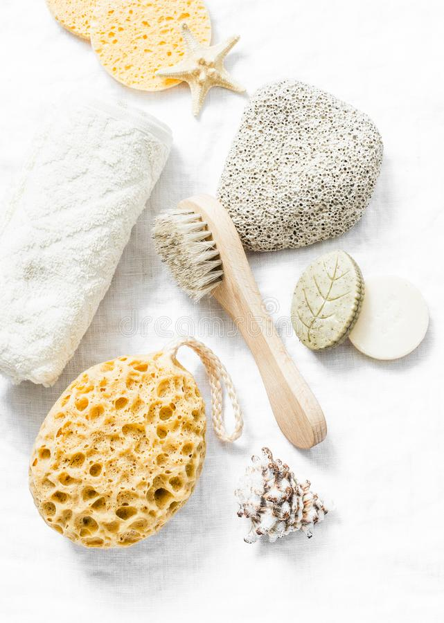 Shower accessories - face brush, sponge, pumice stone, towel, soap on a light background, top view. Cleansing of the skin health c royalty free stock image