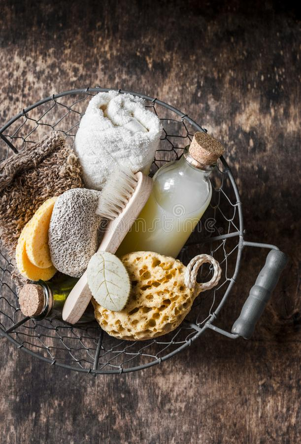 Shower accessories in vintage basket - shampoo, sponge, soap, facial brush, towel, washcloth, pumice stone. Natural beauty care pr stock photo