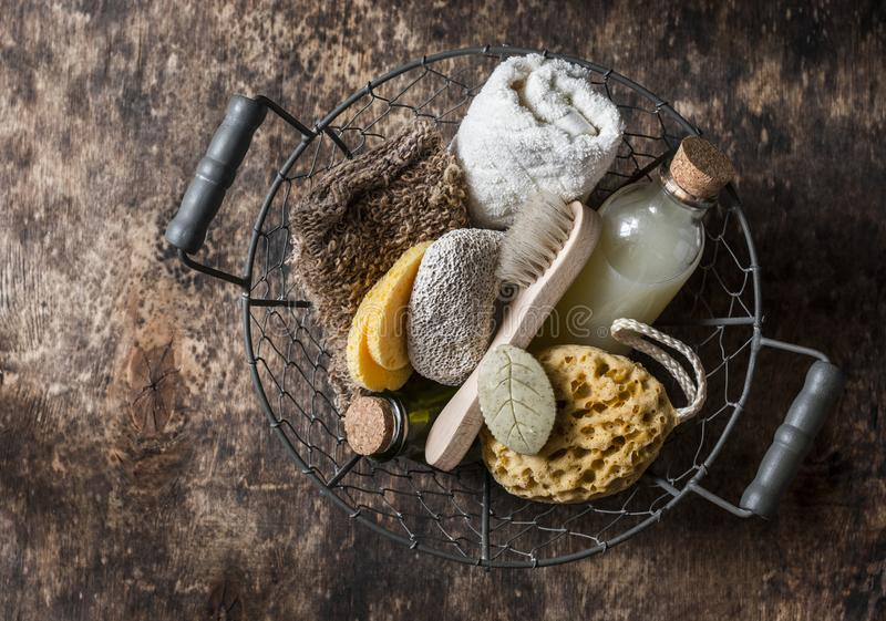 Shower accessories in vintage basket - shampoo, sponge, soap, facial brush, towel, washcloth, pumice stone. Natural beauty care pr royalty free stock image
