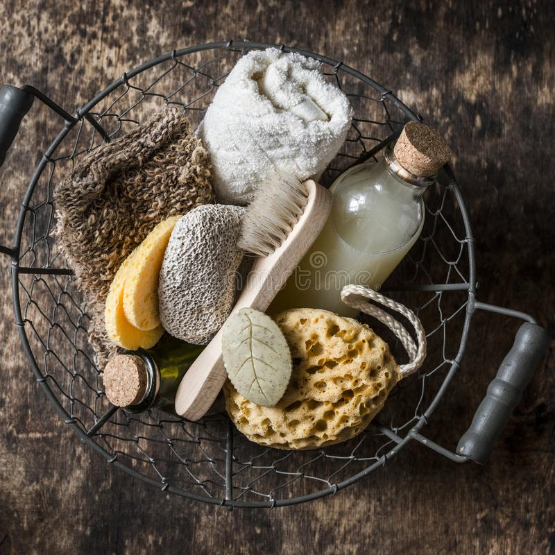 Shower accessories in vintage basket - shampoo, sponge, soap, facial brush, towel, washcloth, pumice stone. On wooden background stock photos