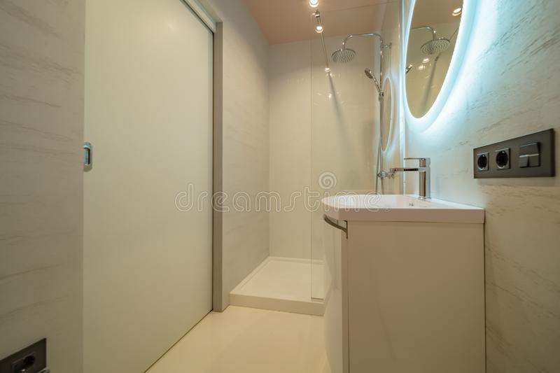 Shower cabin and sink. Small beige tile bathroom with Shower cabin and sink stock image