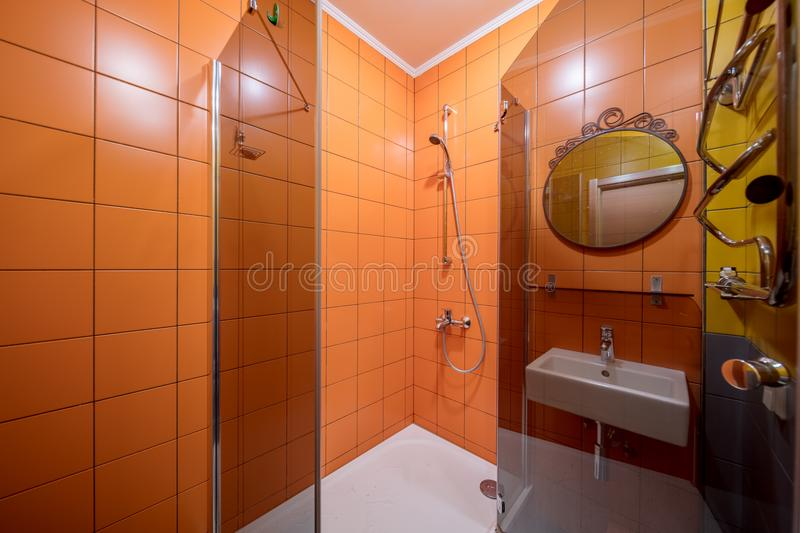 Shower cabin and sink. Small orange tile bathroom with Shower cabin and sink stock photography