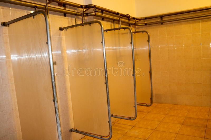 Shower cabins in the dressing rooms of workers at the industrial plant stock image