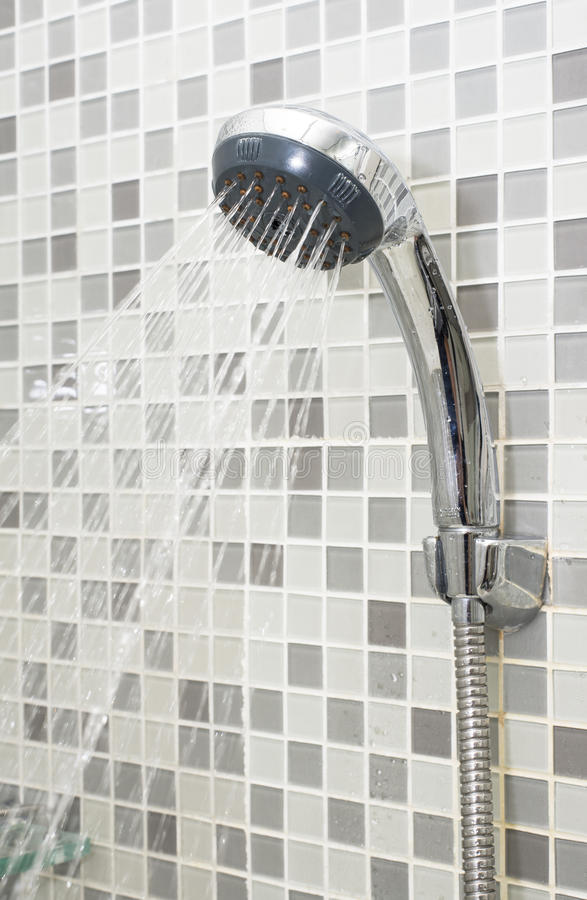 Shower Head. Water flowing from shower head in the bathroom with mosaic style tile stock images