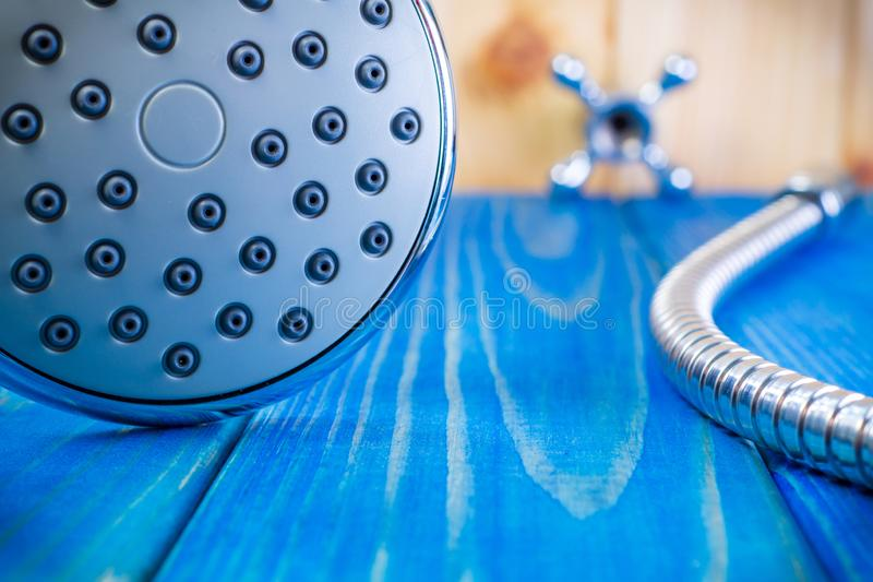 Shower head on blue wooden background and other plumbing parts royalty free stock photos