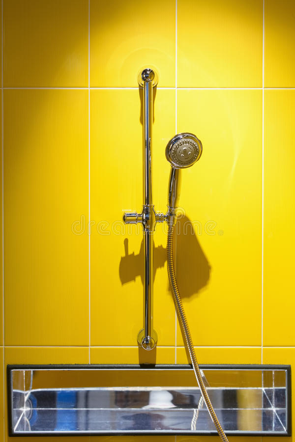 Shower heads. Close up of shower heads with colorful yellow wall tiles stock image