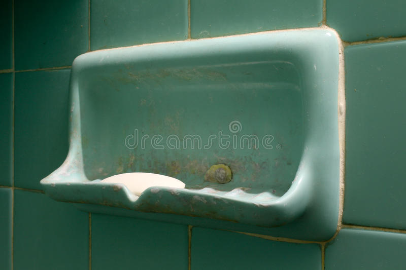 Shower on the holder. Green soap holder on green tile wall in the bathroom stock photos