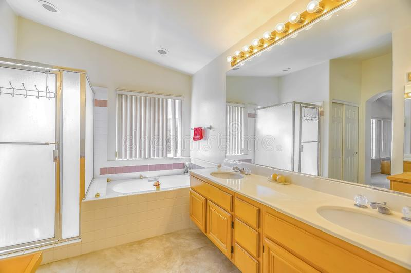 Shower stall built in bathtub and vanity with double sink inside a bathroom. The room is well lighted by light bulbs above the mirror and sunlight streaming in royalty free stock photo
