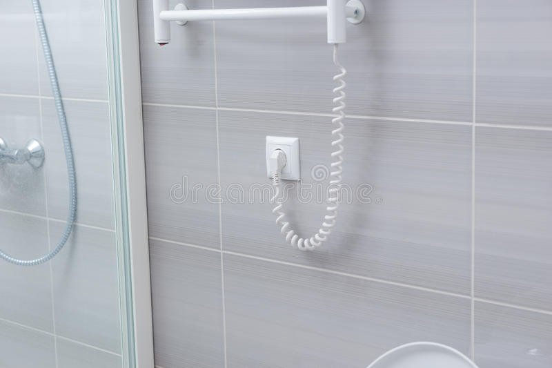 Shower wall with towel warming rack cord. Detail view of spiral shaped power cord for towel warming rack plugged into wall with gray tiles royalty free stock photo