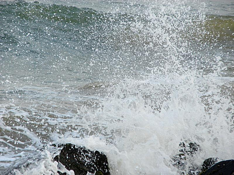 Shower of Water Droplets due to Sea Waves Crashing on Rocks stock image