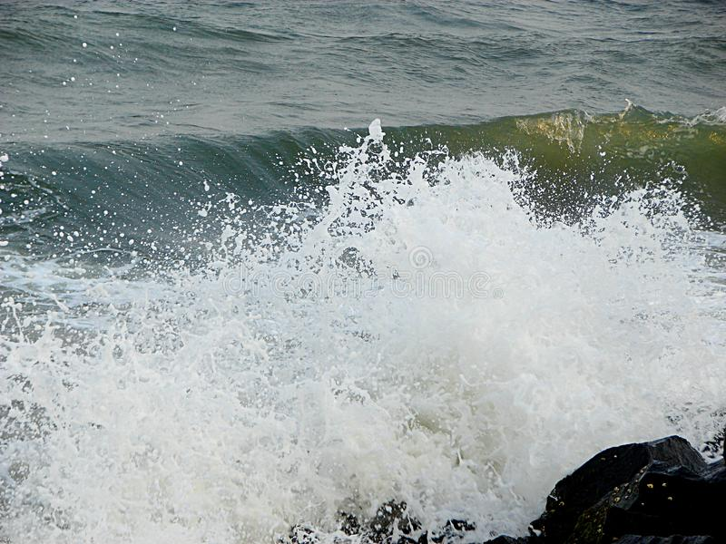Shower of Water Droplets due to Sea Waves Crashing on Rocks royalty free stock photography