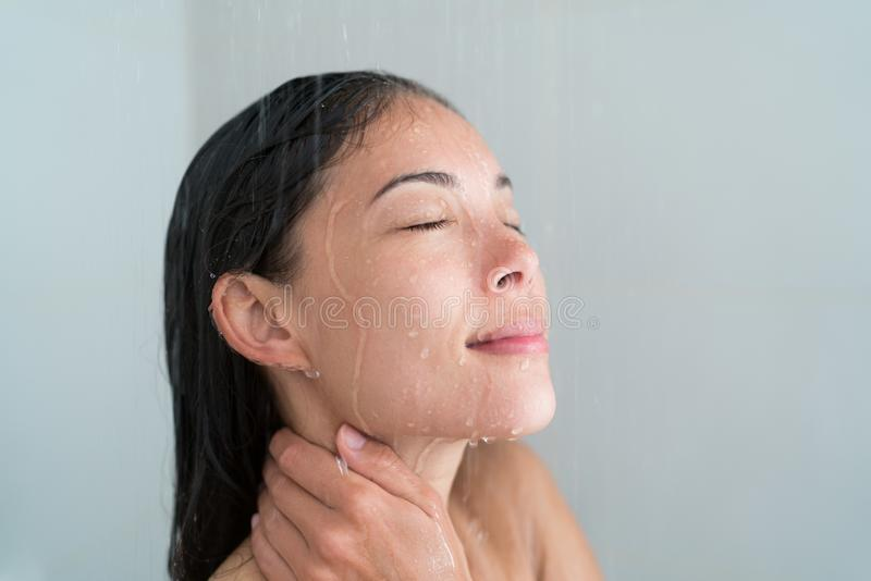 Shower woman showering relaxing washing face. Shower woman showering relaxing under water massaging neck in hot shower. Asian female adult face enjoying spa royalty free stock photo