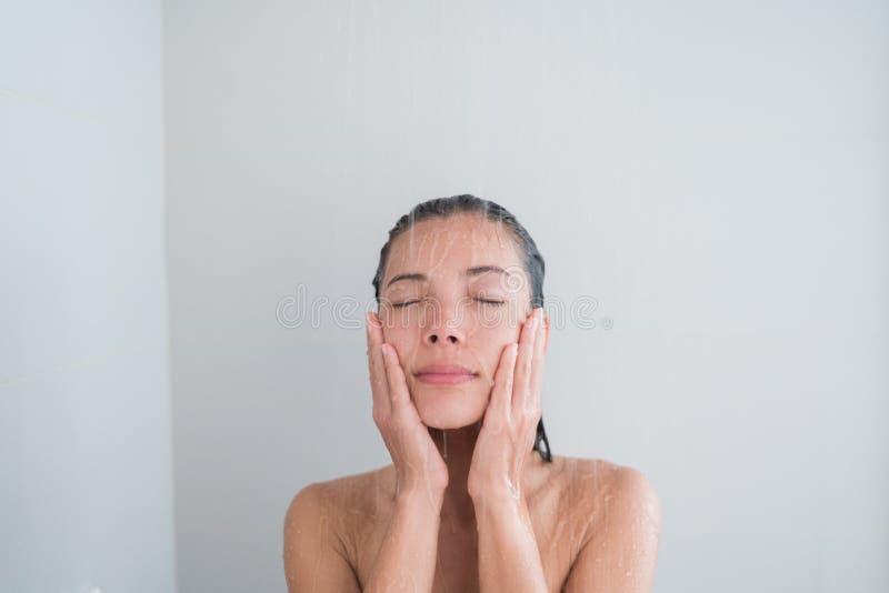 Shower woman showering relaxing washing face. Spa woman showering relaxing under running water in hot shower. Closeup of Asian female adult face enjoying royalty free stock image