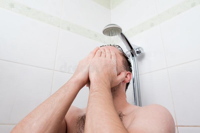 Showering person at home. Young adult body care morning routine. Man taking a shower washing hair under water falling from rain showerhead. Showering person at stock photo