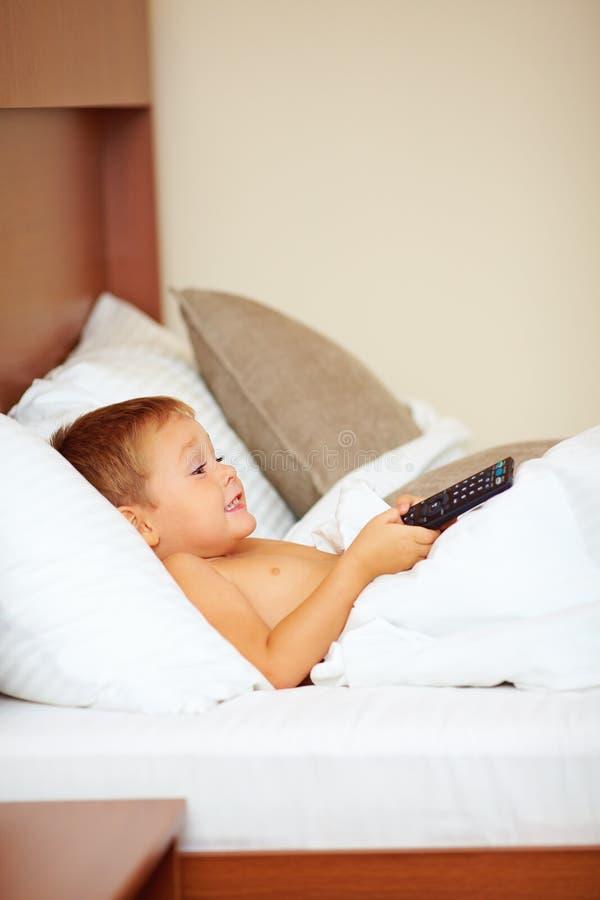 Showes televisivo de observación del entretenimiento del niño en cama foto de archivo libre de regalías