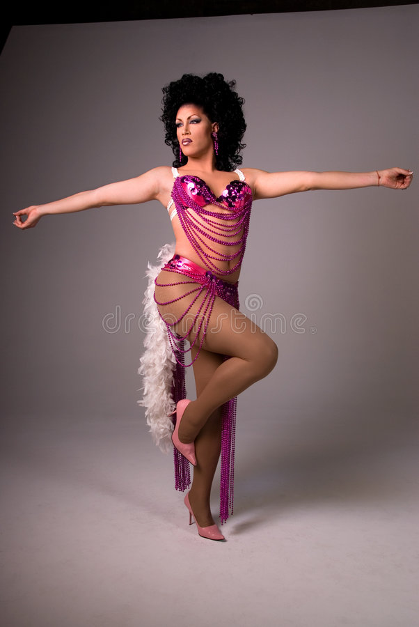 Showgirl Drag queen. Full length shot of a glamorous Drag queen wearing a pink beaded showgirl costume, with both arms out to the side and standing on one leg royalty free stock images