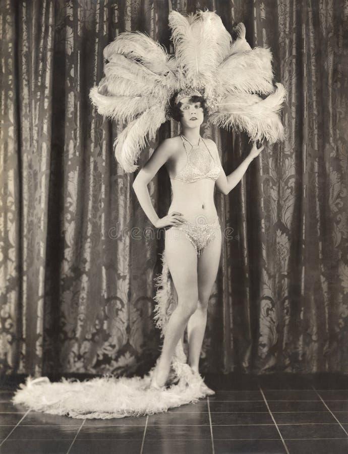 Showgirl wearing feather headdress and sequined bikini stock photos